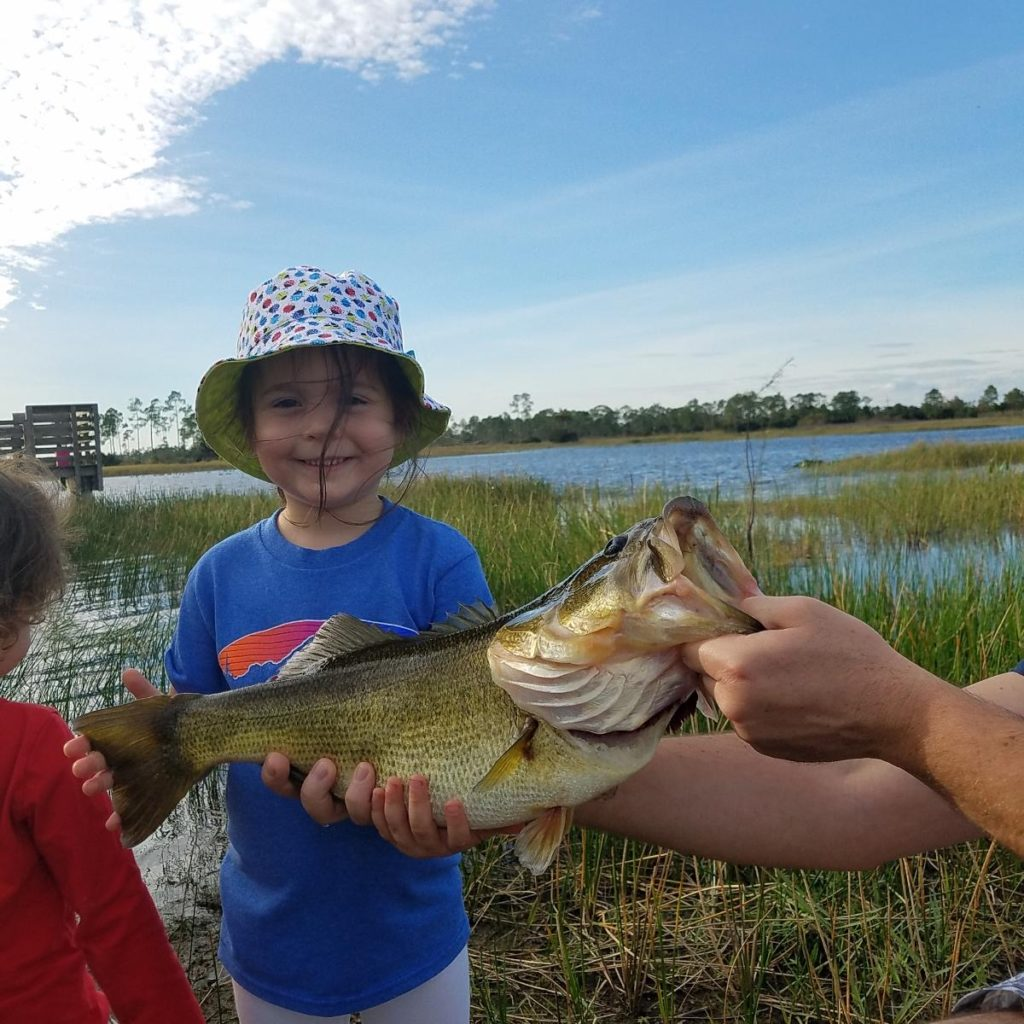 little girl with giant largemouth bass