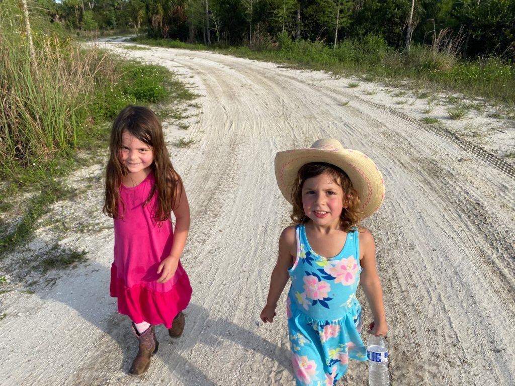Little girls walking down dirt road