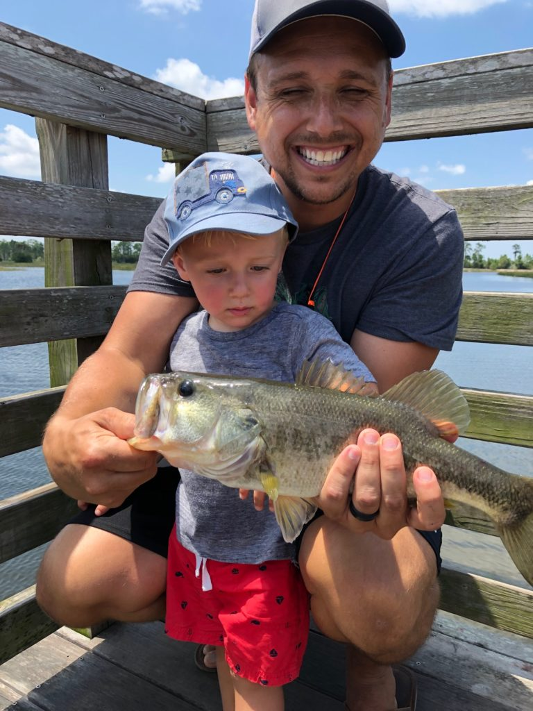 Dad with little boy and largemouth bass