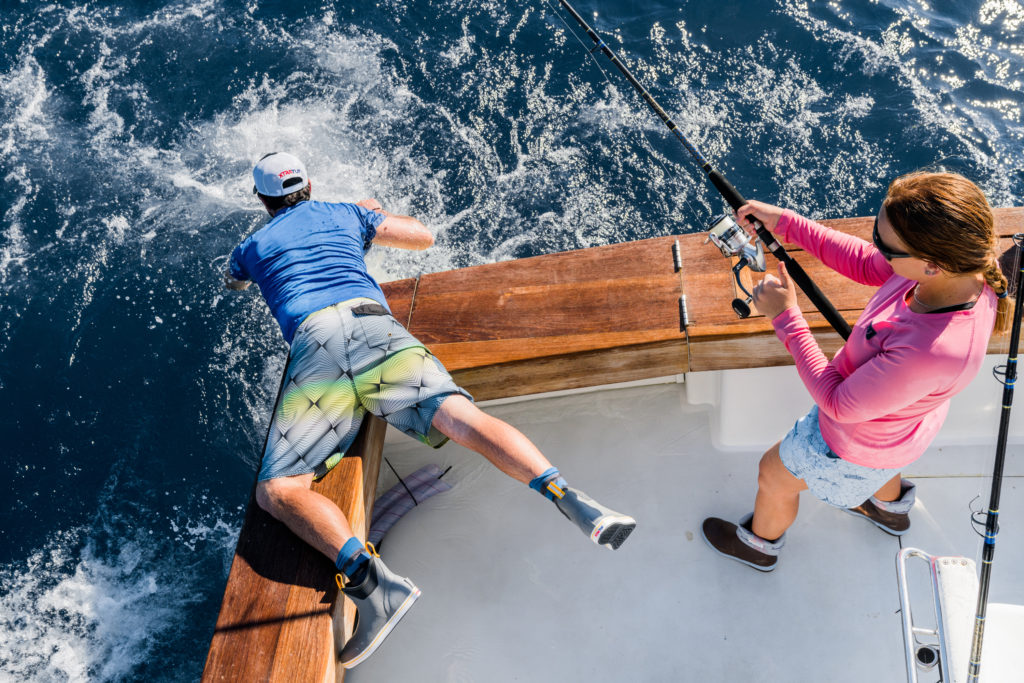 Anglers catching a sailfish while weating Xtratuf boots.