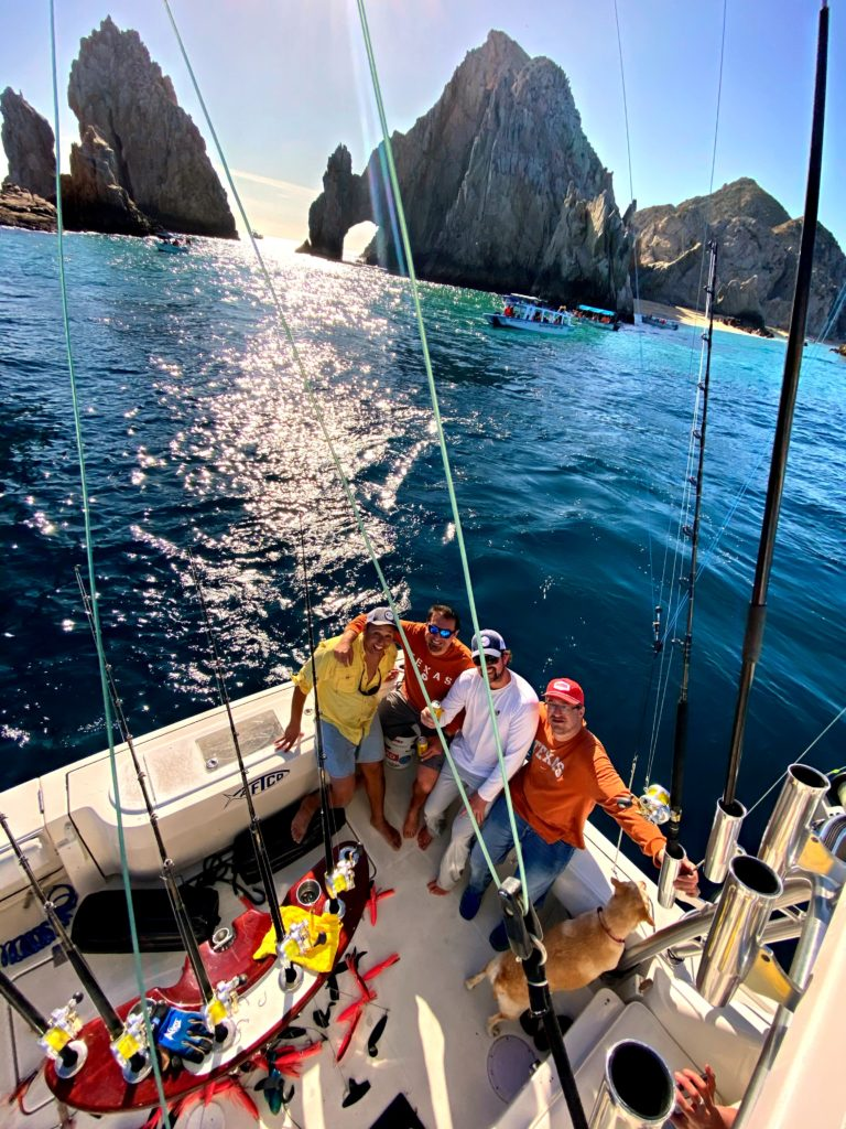 Group of fishermen on boat in front of Land's End in Cabo San Lucas.